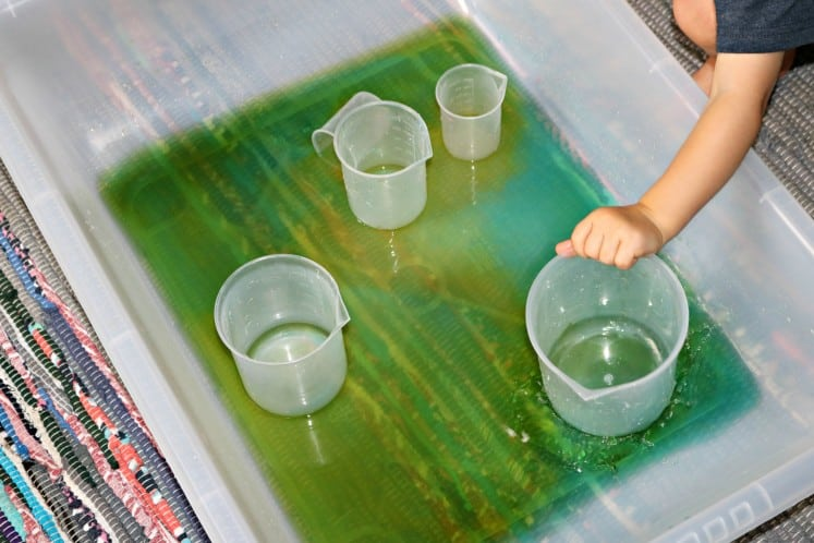 toddler exploring sensory bin filled with colored water and plastic beakers