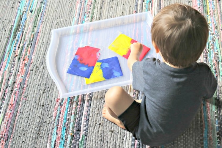toddler boy exploring color mixing with paint in clear zip bags