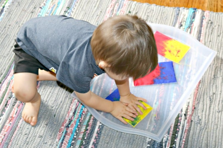 toddler smooshing paint in clear zip bags