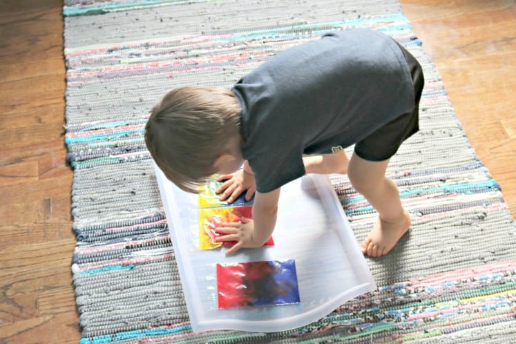 toddler squishing paint in clear zip bags