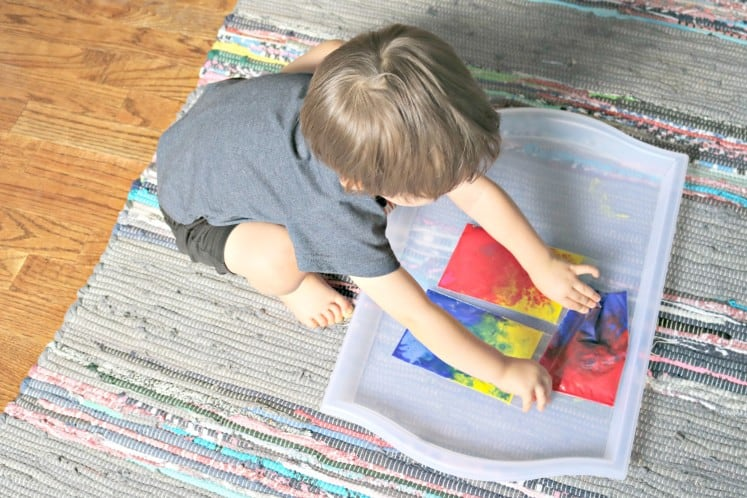 toddler mixing paint colors in clear zip bags
