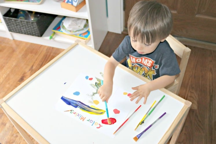 toddler exploring color mixing with paint and an activity sheet