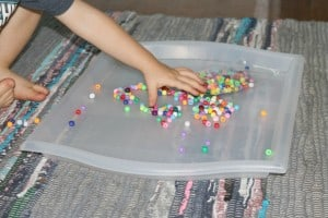 toddler exploring tray filled with beads
