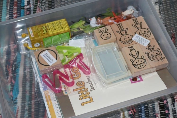 clear drawer filled with Toob figurines, family stamps, letter cookie cutters and Teacher Guides