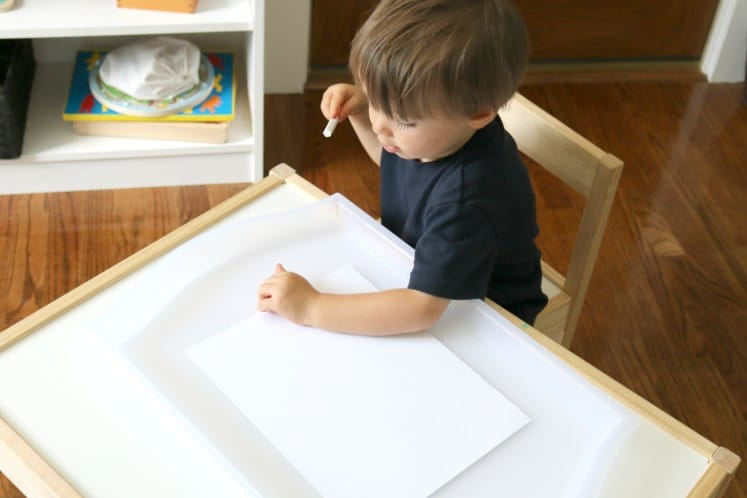 toddler writing on white cardstock with white crayon