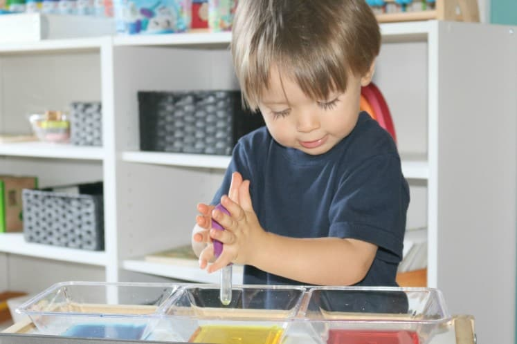 toddler exploring chemical reactions using eyedropper with baking soda and colored vinegar
