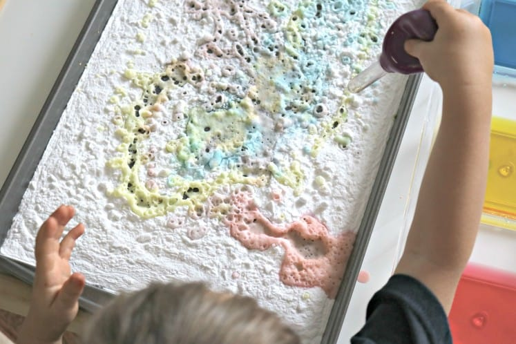 toddler using eyedropper to add colored vinegar to tray filled with baking soda