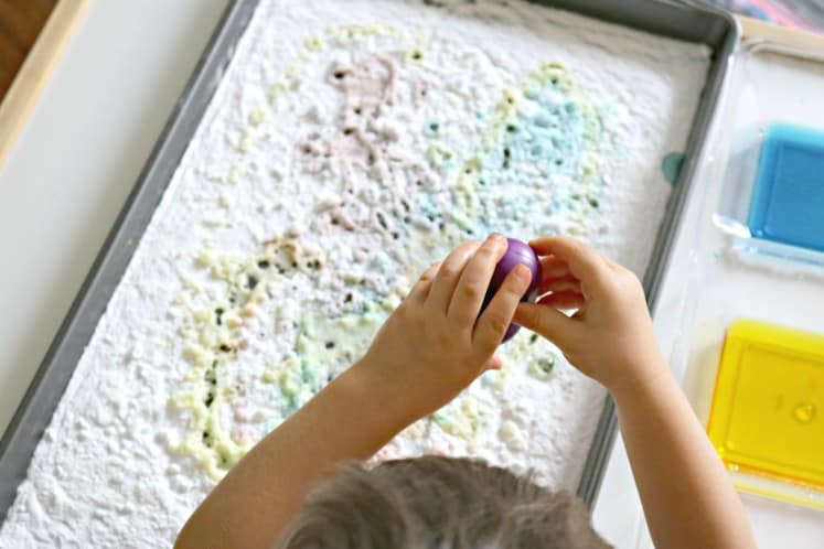 toddler using eyedropper to add colored water on baking soda in tray