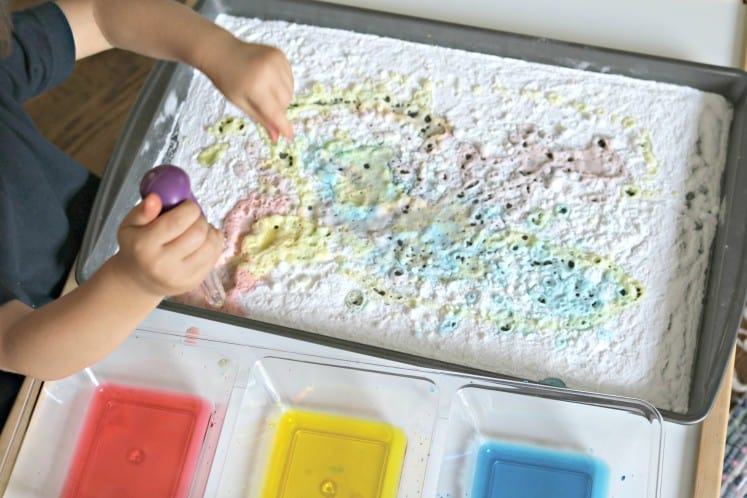 toddler adding colored vinegar to baking soda on cookie sheet