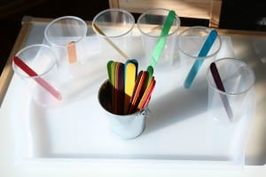 popsicle sticks sorted by color in clear cups
