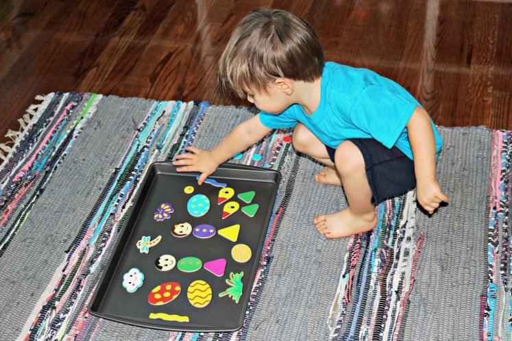 toddler exploring magnetic storytelling pieces on metal cookie sheet