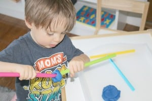 preschooler connecting two colored straws with play dough