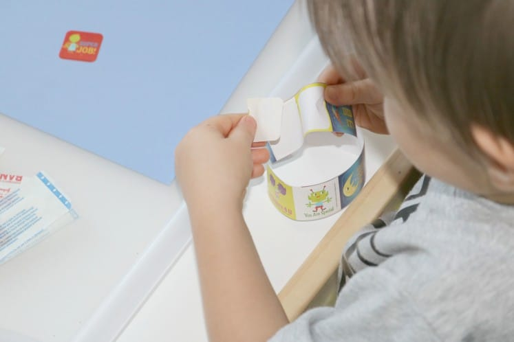 toddler pulling sticker from roll