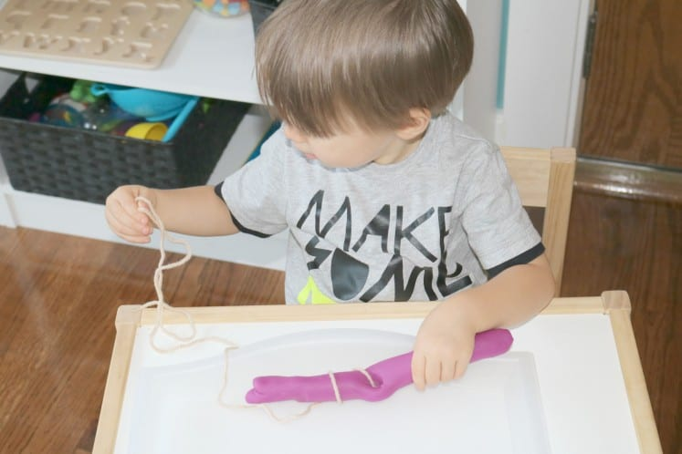 toddler holding string as he wraps it around long piece of play dough
