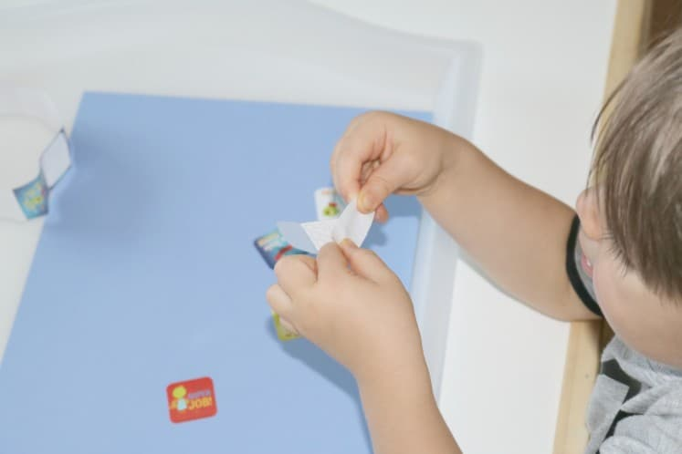 toddler exploring adhesive on sticker