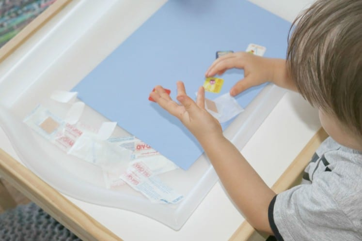 toddler adding stickers to cardstock
