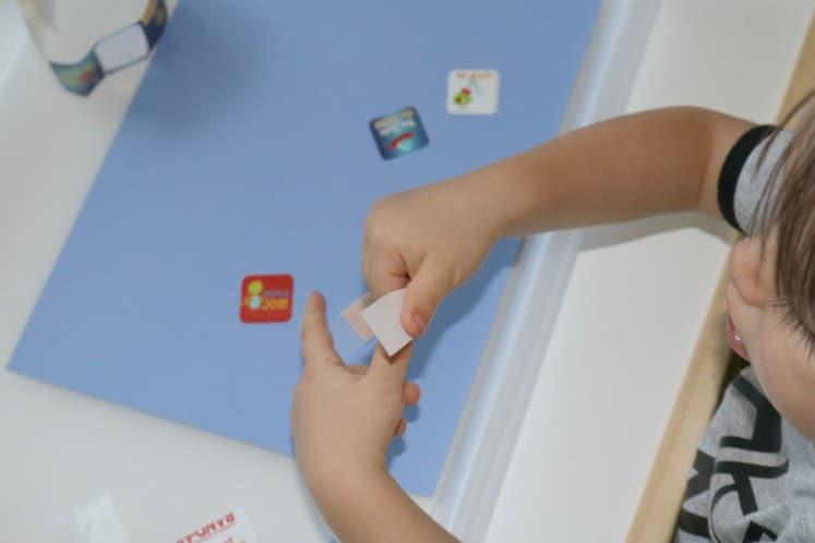 toddler putting sticker on piece of cardstock