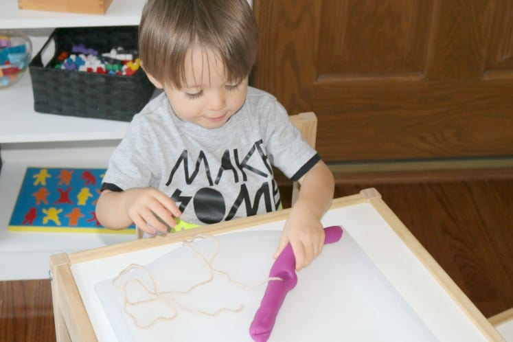 toddler wrapping string around long piece of play dough