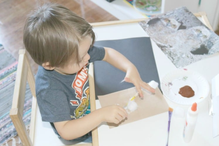 toddler adding cotton balls to outside of paper bag
