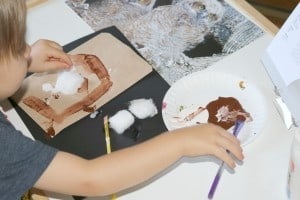 toddler making process art with brown paint