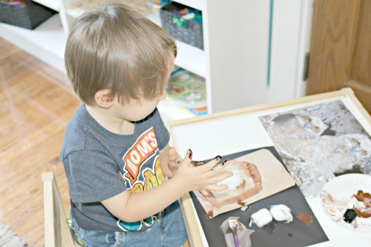 toddler with paint all over hands making owl process art
