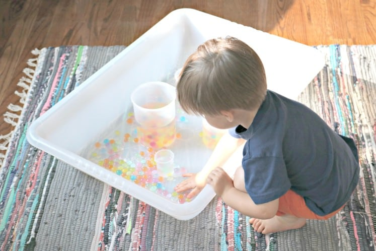 toddler putting hand in sensory bin with rainbow water beads