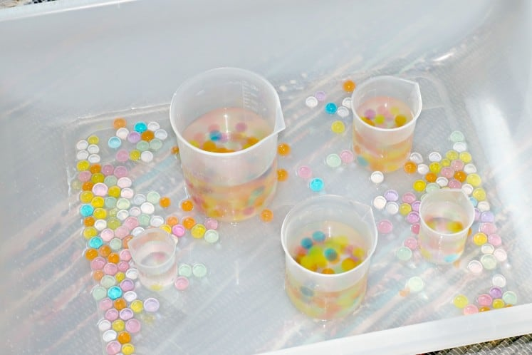 sensory bin with rainbow water beads and plastic beakers