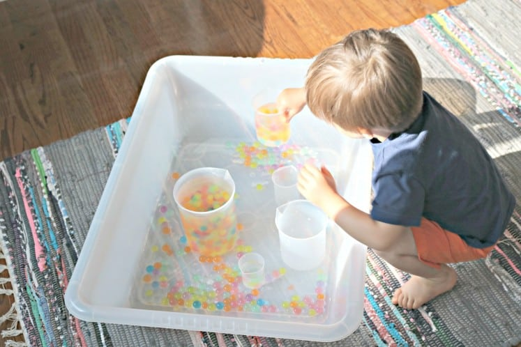 toddler holding plastic beaker filled with rainbow water beads