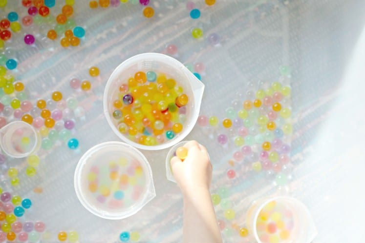 toddler putting rainbow water beads in plastic beaker