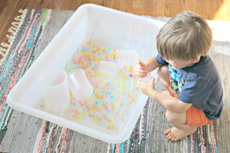 toddler dropping rainbow water beads into plastic beaker