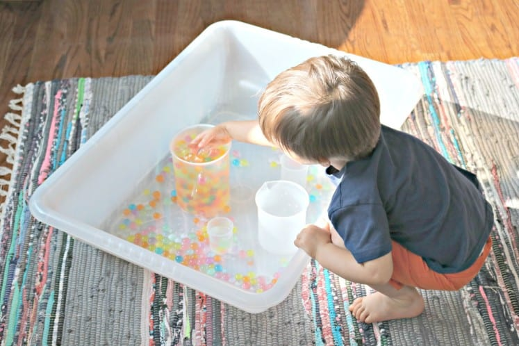 toddler filling plastic beaker with rainbow water beads