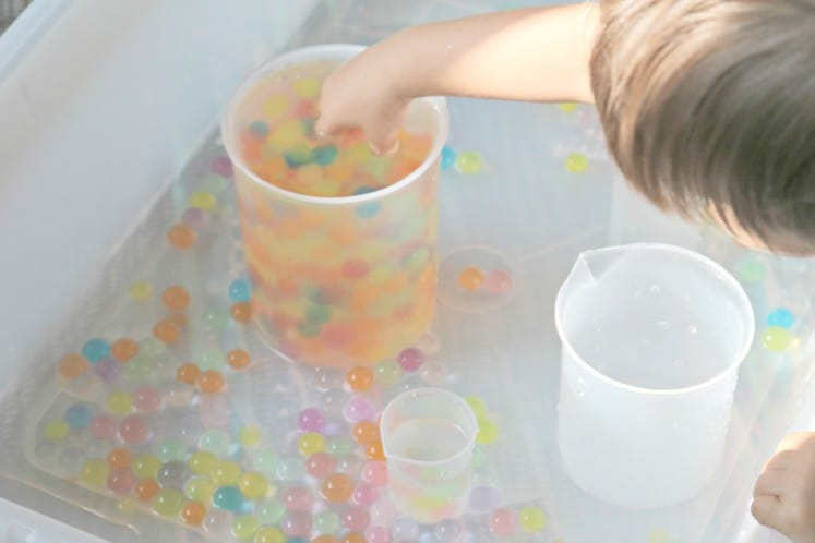 toddler reaching into plastic beaker filled with rainbow water beads