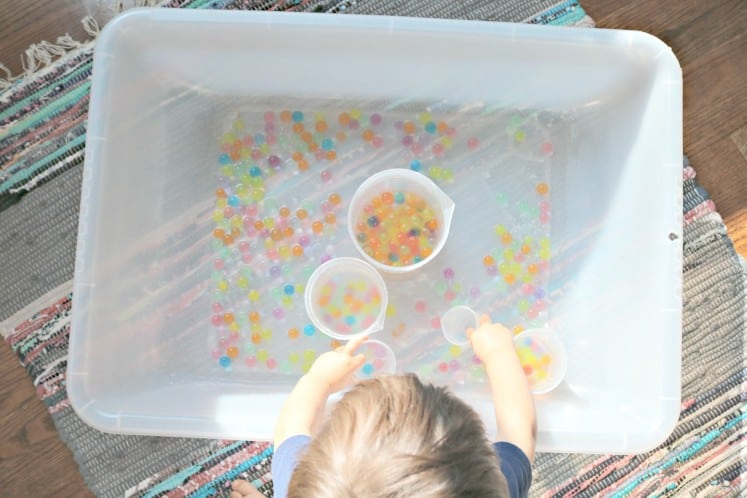 toddler filling multiple plastic beakers with rainbow water beads