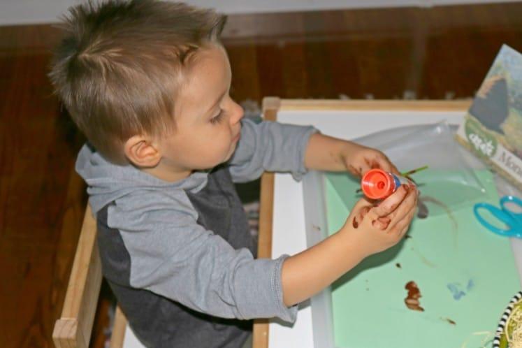 toddler gluing straw on art