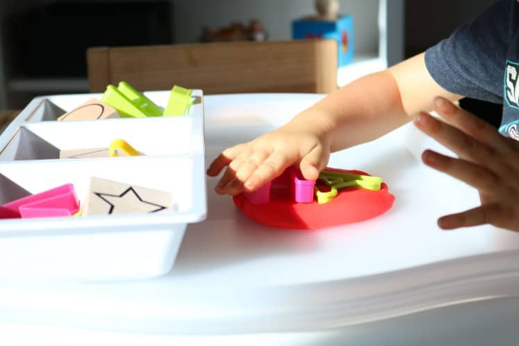 toddler pushing letter cookie cutters into play dough