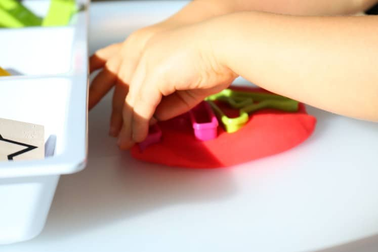 toddler pushing letter cookie cutters into play dough on tray