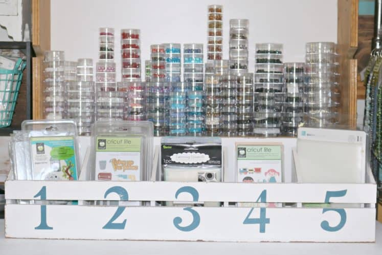 craft dies and Cricut cartridges organized in divided planter box in front of beads organized in clear stacking containers