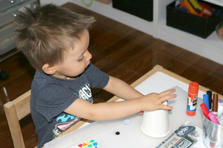 toddler putting stickers on paper cup