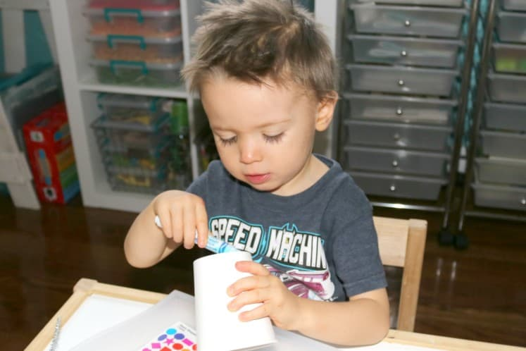 toddler coloring on paper cup with marker