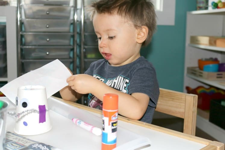 toddler pulling sticker from sheet