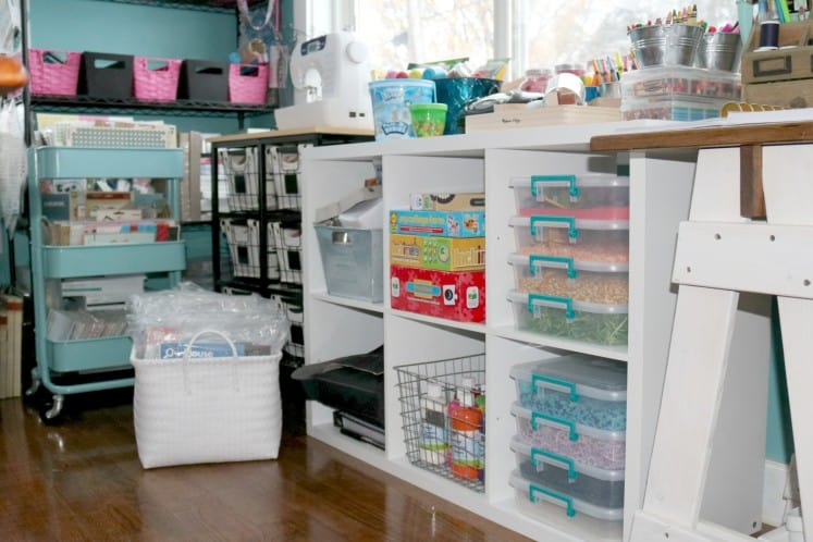 preschooler's art space with cube bookshelf filled with sensory materials, paint, games and art supplies