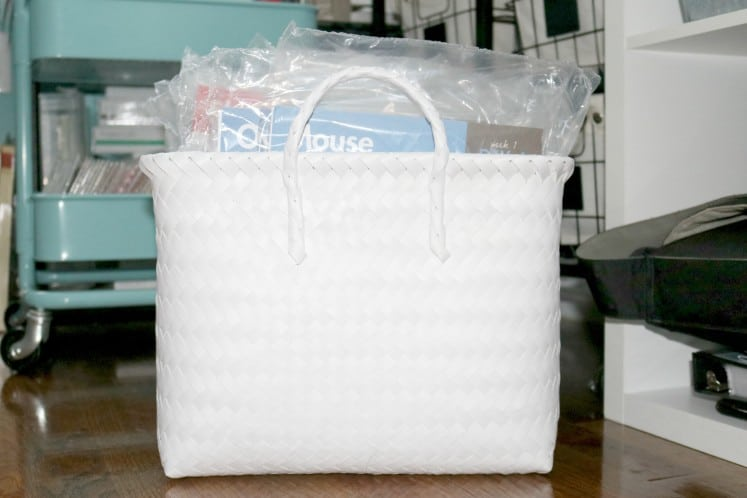 white wicker basket filled with daily discovery bags from Mother Goose Time