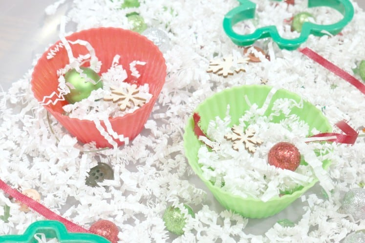 silicone cupcake liners filled with shredded paper, ornaments and wood veneers in Christmas sensory bin