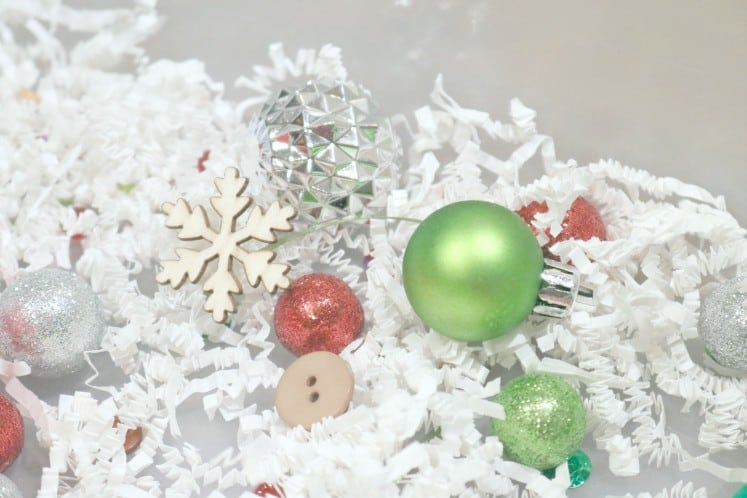 ornaments, wood veneers and buttons in Christmas sensory bin