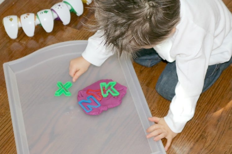 preschooler playing with letter cookie cutters in play dough
