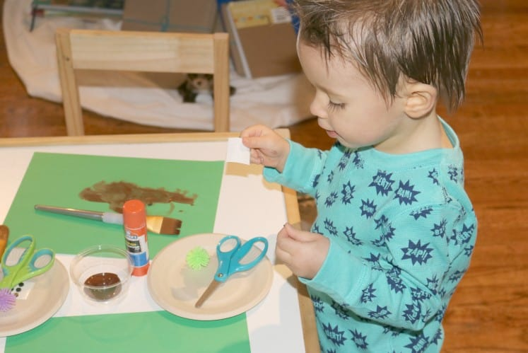 toddler making hedgehog art using paper plate, black dot stickers and other supplies