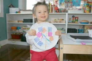 toddler holding paper plate seahorse craft made from gluing colored tissue paper on a paper plate