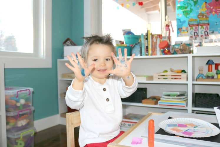 toddler showing off hands covered with paint