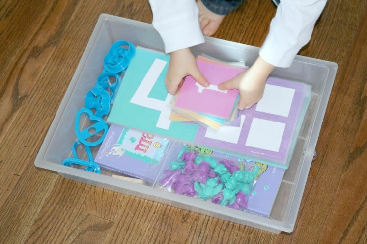 clear plastic drawer filled with preschool math manipulatives, number cookie cutters, and counting cards
