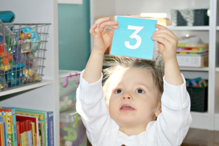 toddler holding number three card above head